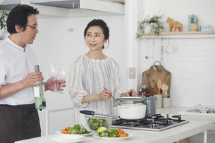 キッチンで料理を作る夫婦の写真素材 [FYI04884498]