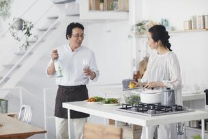 キッチンで料理を作る夫婦の写真素材 [FYI04884500]