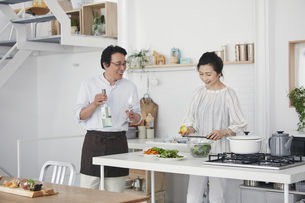 キッチンで料理を作る夫婦の写真素材 [FYI04884502]