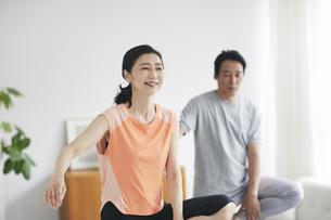 リビングで運動をする夫婦の写真素材 [FYI04884503]