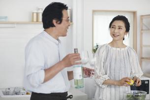 キッチンで料理を作る夫婦の写真素材 [FYI04884504]