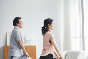リビングで運動をする夫婦の写真素材 [FYI04884505]