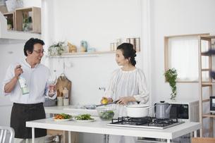 キッチンで料理を作る夫婦の写真素材 [FYI04884506]