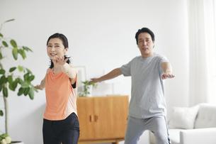 リビングで運動をする夫婦の写真素材 [FYI04884507]