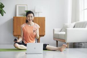 ノートパソコンを見ながらリビングで運動をする女性の写真素材 [FYI04884508]