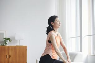 リビングで運動をする女性の写真素材 [FYI04884510]
