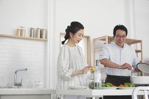 キッチンで料理を作る夫婦の写真素材 [FYI04884511]