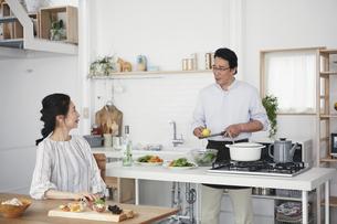 キッチンで料理を作る夫婦の写真素材 [FYI04884513]