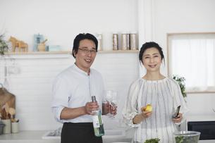 キッチンで料理を作る夫婦の写真素材 [FYI04884514]