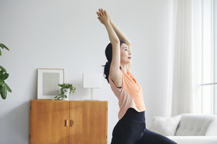 リビングで運動をする女性の写真素材 [FYI04884515]