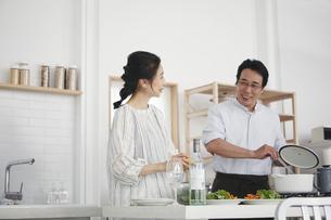 キッチンで料理を作る夫婦の写真素材 [FYI04884516]