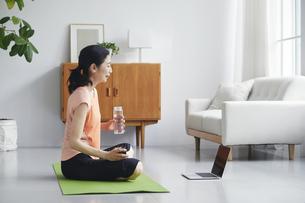 ノートパソコンを見ながらリビングで運動をする女性の写真素材 [FYI04884519]
