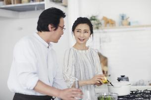 キッチンで料理を作る夫婦の写真素材 [FYI04884520]