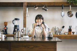 落ち着いた雰囲気の空間で、コーヒーを淹れて飲む若い女性の写真素材 [FYI04884525]