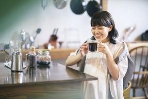 落ち着いた雰囲気の空間で、コーヒーを淹れて飲む若い女性の写真素材 [FYI04884528]