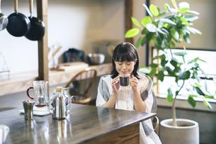 落ち着いた雰囲気の空間で、コーヒーを淹れて飲む若い女性の写真素材 [FYI04884529]