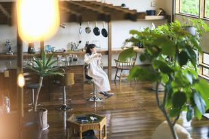落ち着いた雰囲気の空間で、コーヒーを淹れて飲む若い女性の写真素材 [FYI04884536]