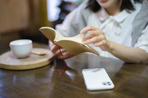 暖かい雰囲気の空間で、本を読む若い女性の手元の写真素材 [FYI04884538]