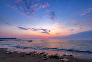 犬吠埼長崎海水浴場から 太平洋からの日の出に朝焼けに染まる海・朝焼けの空輝く雲の写真素材 [FYI04884542]