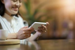 暖かい雰囲気の空間で、スマートフォンの画面を見る若い女性の写真素材 [FYI04884548]
