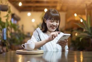 暖かい雰囲気の空間で、スマートフォンの画面を見る若い女性の写真素材 [FYI04884551]