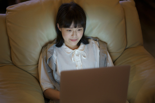 ひかえめな照明の部屋のソファで、ノートパソコンを使う若い女性の写真素材 [FYI04884564]