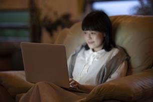 ひかえめな照明の部屋のソファで、ノートパソコンを使う若い女性の写真素材 [FYI04884567]