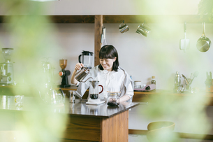 おしゃれな空間で、コーヒーを淹れる若い女性の写真素材 [FYI04884993]