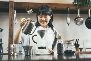 おしゃれな空間で、コーヒーを淹れる若い女性の写真素材 [FYI04884997]