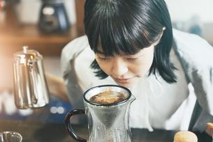 おしゃれな空間で、コーヒーを淹れる若い女性の写真素材 [FYI04884998]