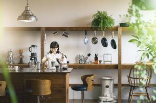 おしゃれな空間で、コーヒーを淹れる若い女性の写真素材 [FYI04885002]
