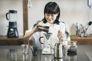 おしゃれな空間で、コーヒーを淹れる若い女性の写真素材 [FYI04885005]