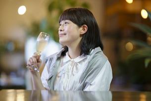 暖かい雰囲気の空間で、シャンパングラスを持つ若い女性の写真素材 [FYI04885045]