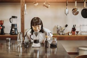 落ち着いた空間で、コーヒーを淹れる若い女性の写真素材 [FYI04885154]