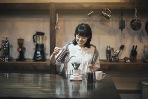 落ち着いた空間で、コーヒーを淹れる若い女性の写真素材 [FYI04885157]
