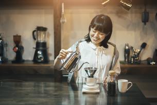 落ち着いた空間で、コーヒーを淹れる若い女性の写真素材 [FYI04885160]