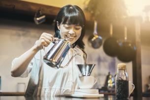落ち着いた空間で、コーヒーを淹れる若い女性の写真素材 [FYI04885164]