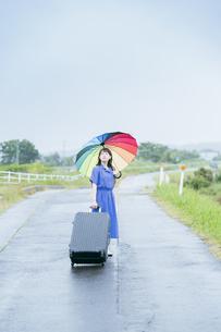 スーツケースとカラフルな傘を持つ女性の写真素材 [FYI04885166]