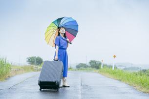 スーツケースとカラフルな傘を持つ女性の写真素材 [FYI04885168]