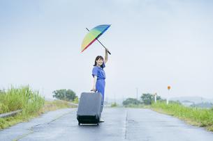 スーツケースとカラフルな傘を持つ女性の写真素材 [FYI04885172]
