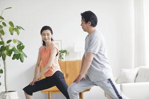 リビングで運動をする夫婦の写真素材 [FYI04885294]