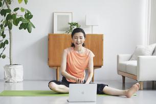 ノートパソコンを見ながらリビングで運動をする女性の写真素材 [FYI04885295]