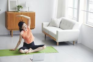 ノートパソコンを見ながらリビングで運動をする女性の写真素材 [FYI04885300]