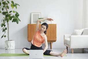 ノートパソコンを見ながらリビングで運動をする女性の写真素材 [FYI04885302]
