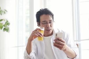 ビールを飲みながらスマホを見る男性の写真素材 [FYI04885310]