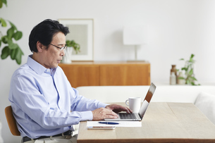 ノートパソコンを見ながら仕事をする男性の写真素材 [FYI04885314]