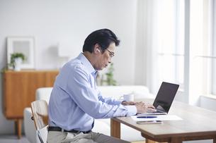 ノートパソコンを見ながら仕事をする男性の写真素材 [FYI04885315]
