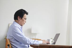 ノートパソコンを見ながら仕事をする男性の写真素材 [FYI04885317]