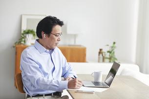 ノートパソコンを見ながら仕事をする男性の写真素材 [FYI04885319]