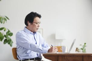 ノートパソコンを見ながら仕事をする男性の写真素材 [FYI04885322]
